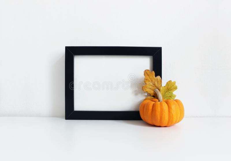 Black blank wooden frame mockup with an orange pumpkin and golden oak leaves lying on the white table. Poster product royalty free stock photography