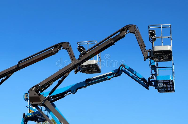 Black and blue aerial work platforms of cherry picker against blue sky. Black and blue aerial work platforms of cherry picker on blue sky background royalty free stock photography