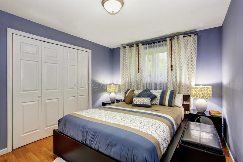Black and blue bedroom interior with built-in wardrobe and hardwood floor. stock photos