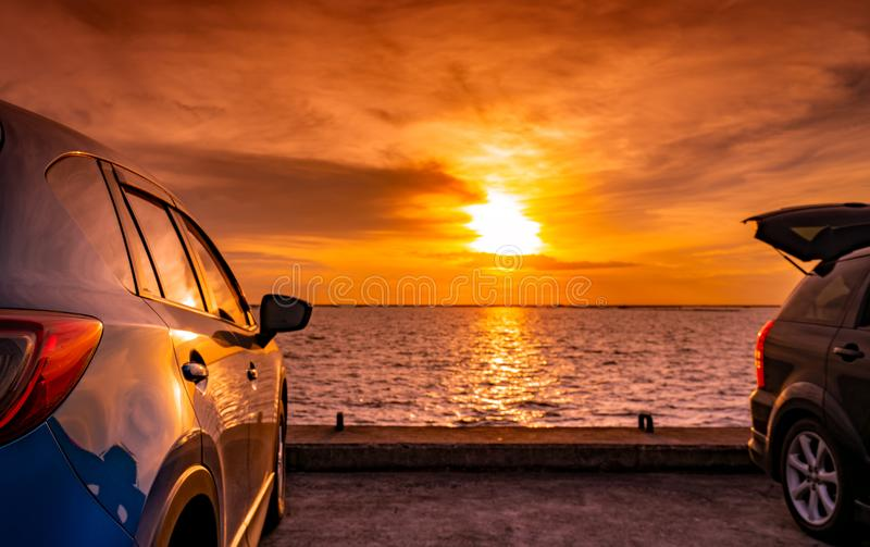 Black and blue SUV car with sport and modern design parked on concrete road by the sea at sunset. Environmentally friendly. Technology. Road trip travel on stock photo