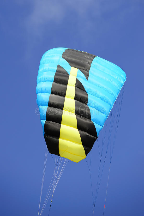 Black, blue and yellow kite in the blue sky. The kite of a kitesurfer against an airfine blue sky stock photography