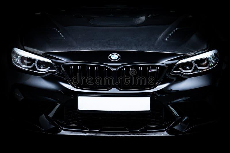 Черный BMW M2 застрелили в гараже. Черный BMW M2 с капотом из углеродного волокна снятый в гараже со студийным оборудованием стоковая фотография без роялти