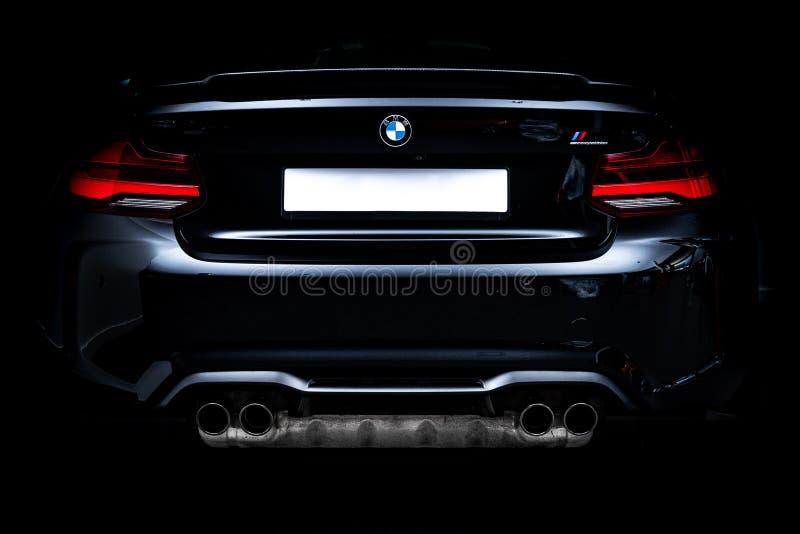 Черный BMW M2 застрелили в гараже. Черный BMW M2 с капотом из углеродного волокна снятый в гараже со студийным оборудованием стоковые фотографии