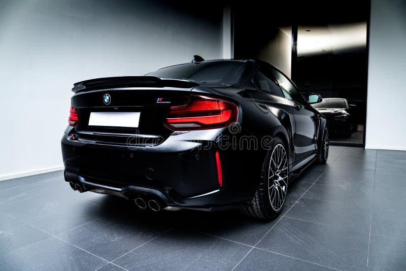 Черный BMW M2 застрелили в гараже. Черный BMW M2 с капотом из углеродного волокна снятый в гараже со студийным оборудованием стоковое фото