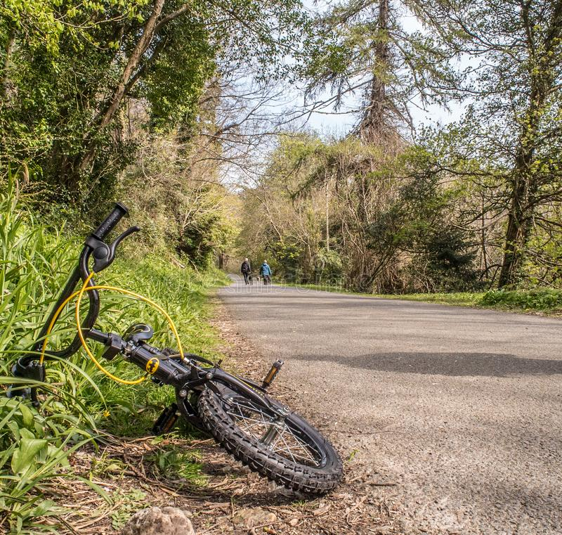 A Black BMX Bike on a Roadside. Black BMX bike with batman symbol lays on it`s side at the edge of a road surrounded by trees, as people walk their dogs in the stock images