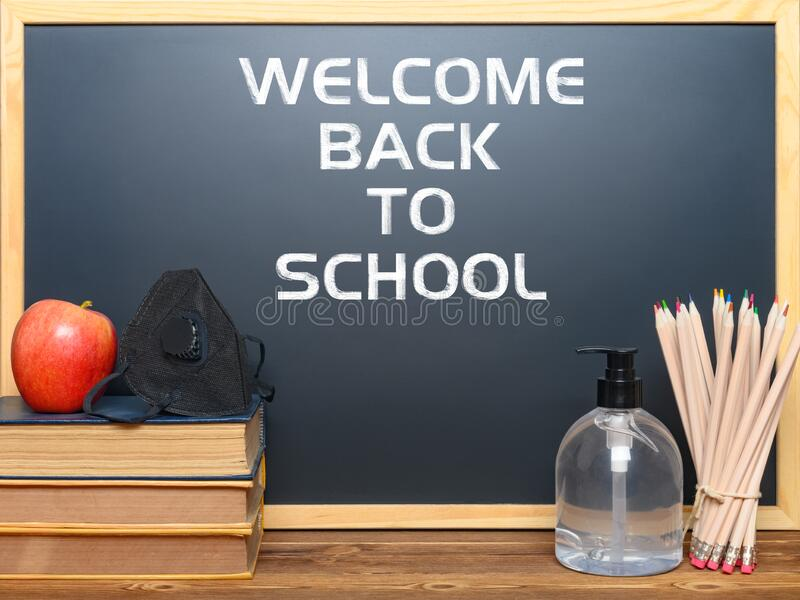 Black board with back to school & safety mask for children and instant hand sanitizer nearby, removeable words contain paths, stock image