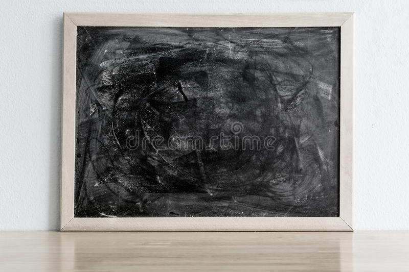 Black board with chalk rubbed out on wood table. Blank frame for stock photo