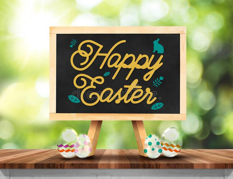 Black board with Happy Easter word an eggs on wooden plank table royalty free stock photography
