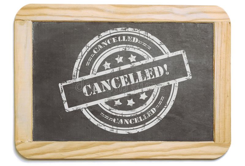 Black board with layered chalk message. Black board with wooden frame, layered grund design chalk message in stamp form: Cancelled. Isolated on white background royalty free stock image