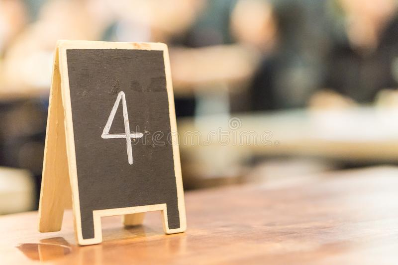 Black board number four on the table in restaurant royalty free stock image