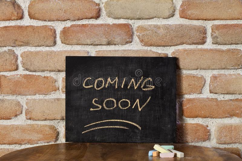 Black board with the phrase COMING SOON drown by hand on wooden table on brick wall background. Presentation concept stock photos