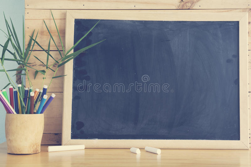 Black board and stack of pen on wooden table. stock images