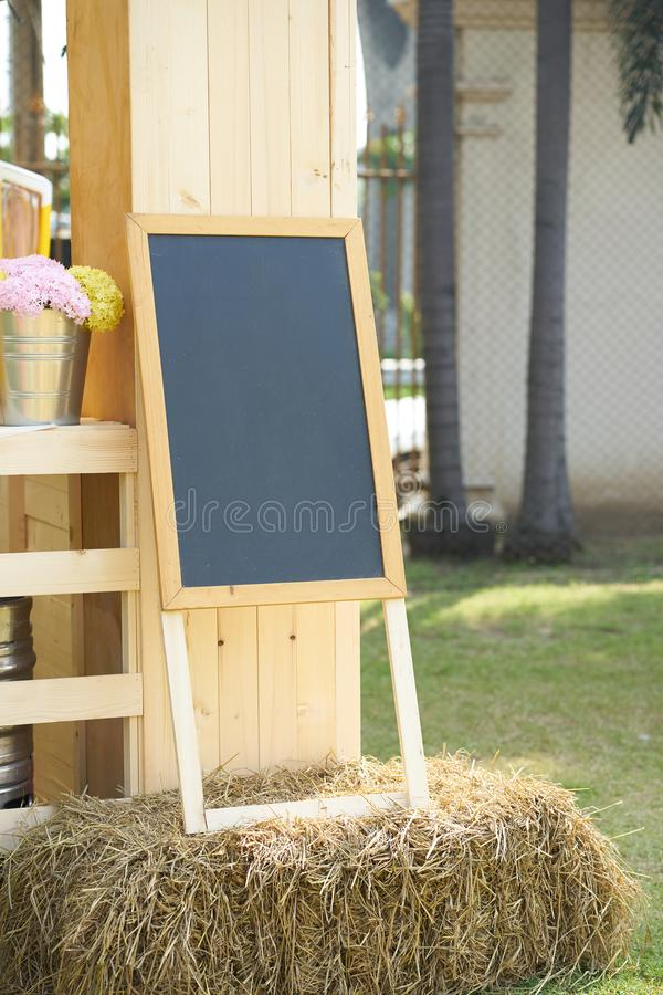 Black board stand on straw decorate with flowers vase stock image