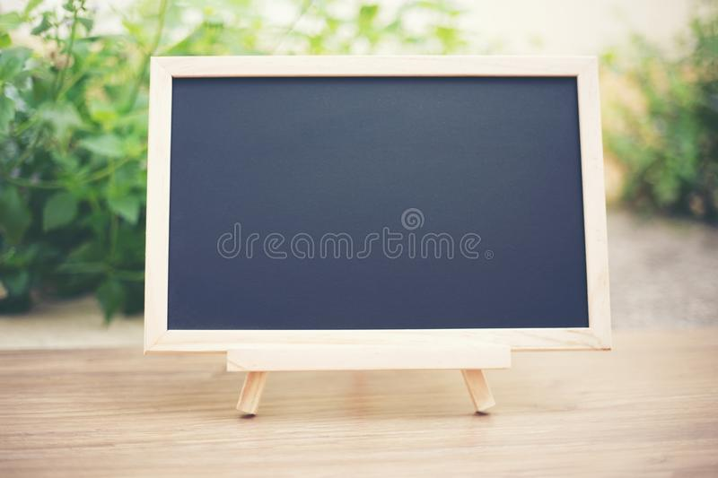 Black board on wood table top with sun and blur green tree boke royalty free stock photos