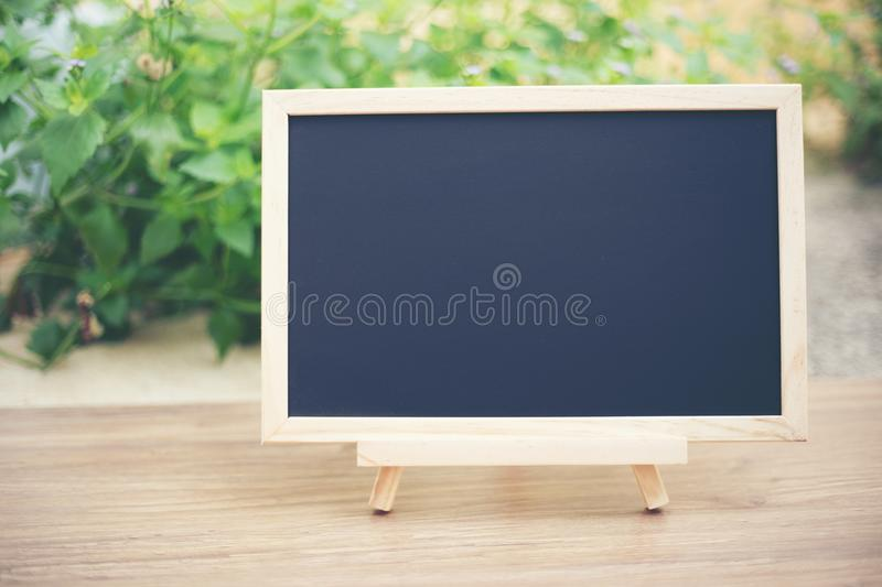 Black board on wood table top with sun and blur green tree boke stock image