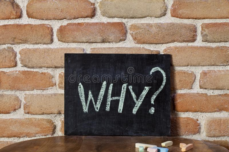 Black board with the word WHY? drown by hand on wooden table on brick wall background stock images