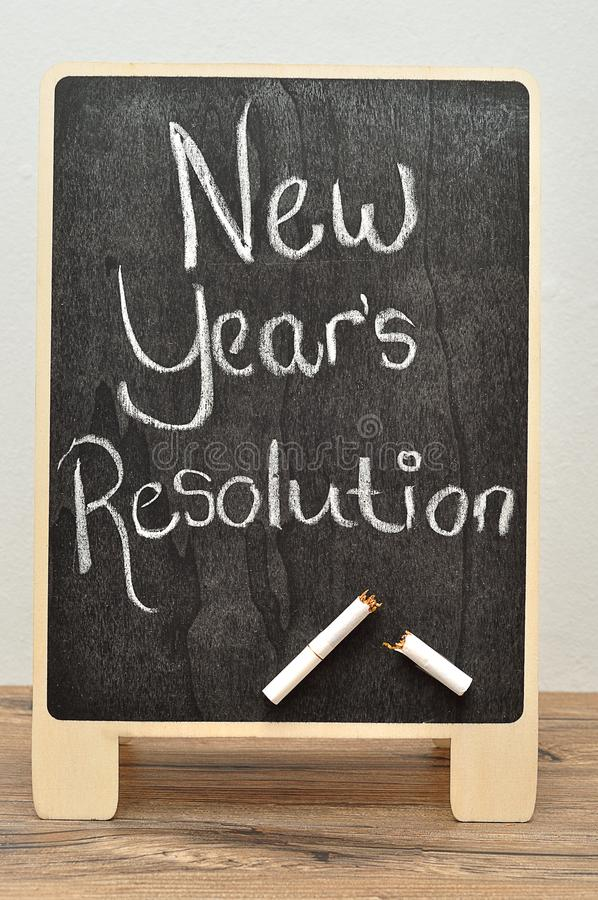 A black board with the words new years resolution and a cigarette broken in two. On a table royalty free stock photography