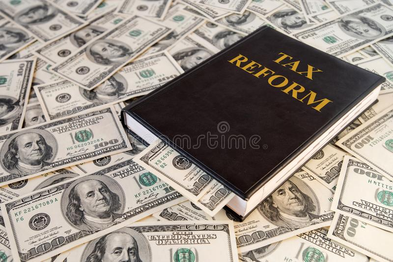 Black book and money with the inscription Tax Reform on dollar banknotes background royalty free stock image