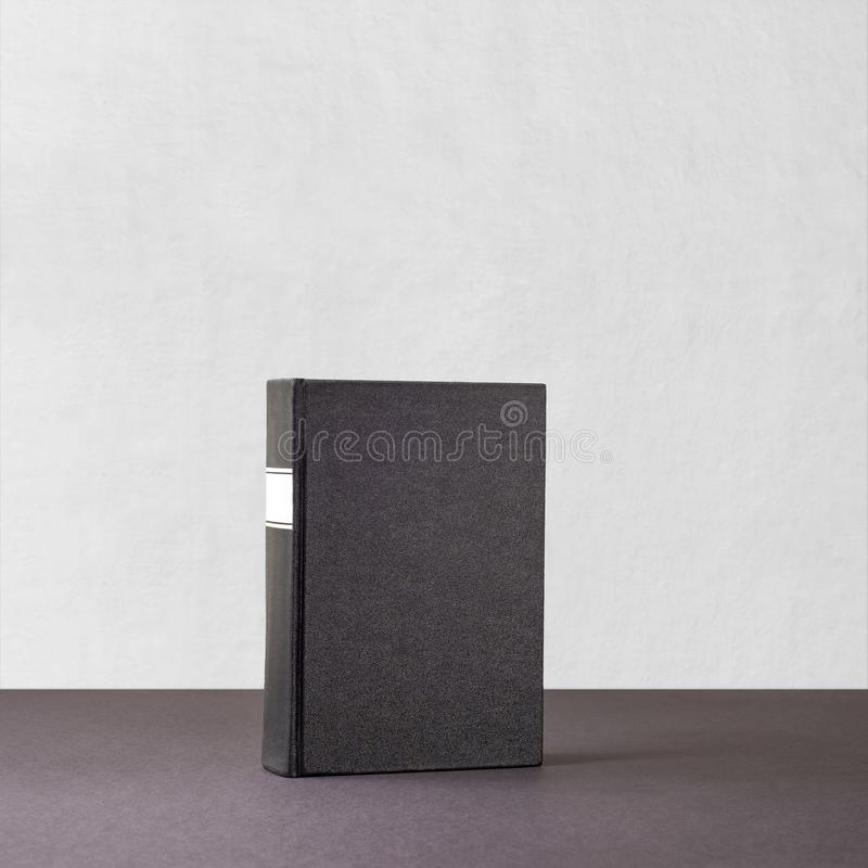 Black book with white frame on spine standing on dark surface stock photos