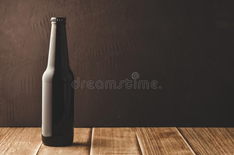 Black bottle of beer on a dark background/black bottle of beer on a dark background. Copy space royalty free stock photos