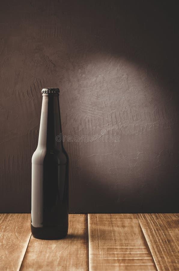 black bottle of beer on a dark background/black bottle of beer on a dark background of a wooden shelf. Selective focus and stock image