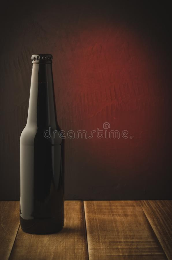 black bottle of beer on a red background of a wooden shelf/black bottle of beer on a red background of a wooden shelf. Selective stock photos