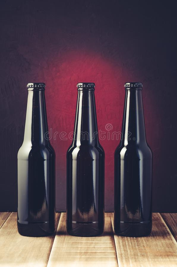 black bottle of beer on a red background of a wooden shelf/black bottle of beer on a red background of a wooden shelf. Toned and stock image