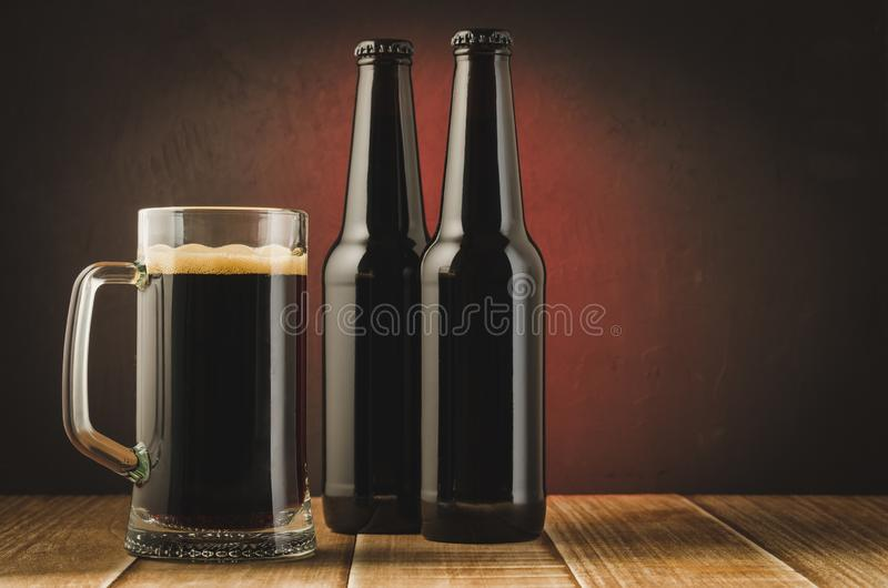 black bottle and glass beer on a dark background with red light/black bottle and glass beer on a dark background with red light. royalty free stock image