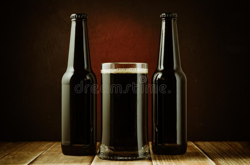 black bottle and glass beer on a red background/ black bottle and glass beer on a red background of a wooden shelf royalty free stock images
