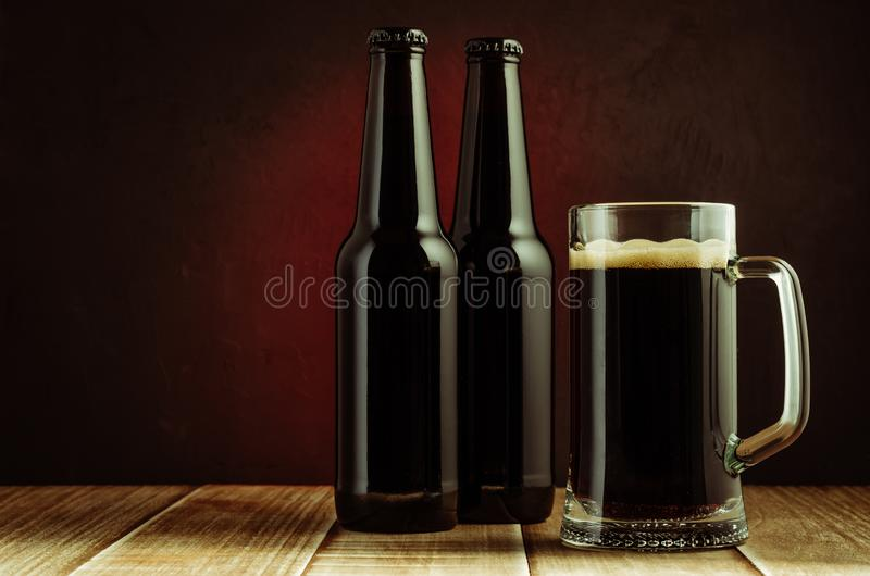 black bottle and glass beer on a red background/black bottle and glass beer on a red background of a wooden shelf. Copyspace and royalty free stock image