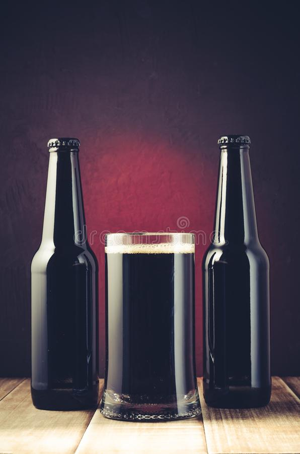 black bottle and glass beer on a red background/black bottle and glass beer on a red background of a wooden shelf. Toned royalty free stock photo