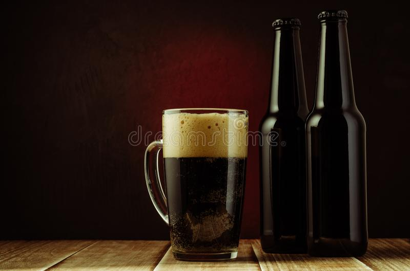 black bottle and glass beer on a red background of a wooden shelf/black bottle and glass beer on a red background of a wooden stock photos