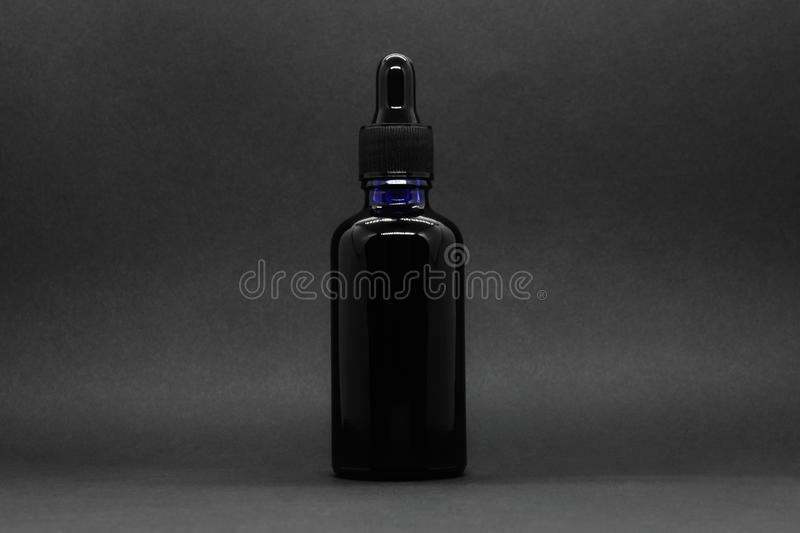 Black bottle with pipette gag on black background with copy space.  royalty free stock photography