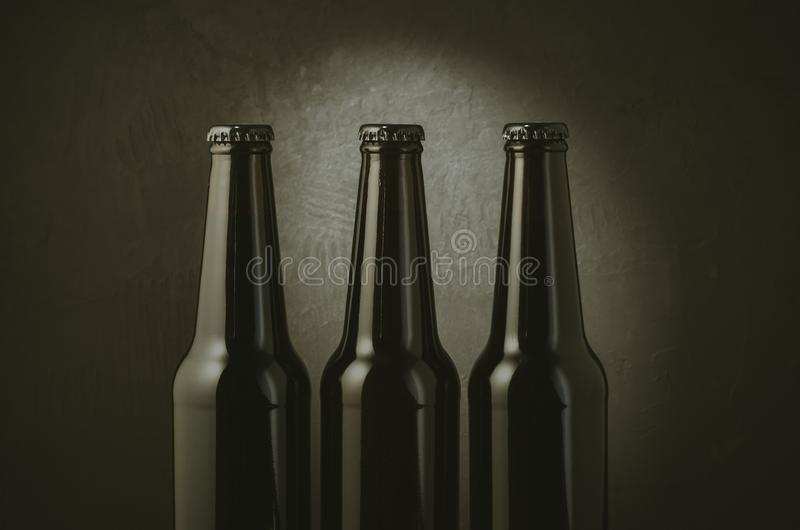 black bottles of beer on a dark background with light/black bottles of beer on a dark background with light. Selective focus royalty free stock photos