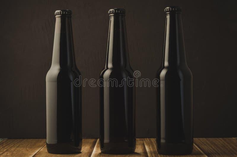 black bottles of beer on a wooden table against a dark background/black bottles of beer on a wooden table against a dark stock photos