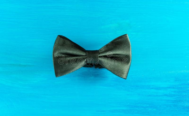 Black bow tie. On turquoise wooden background royalty free stock image