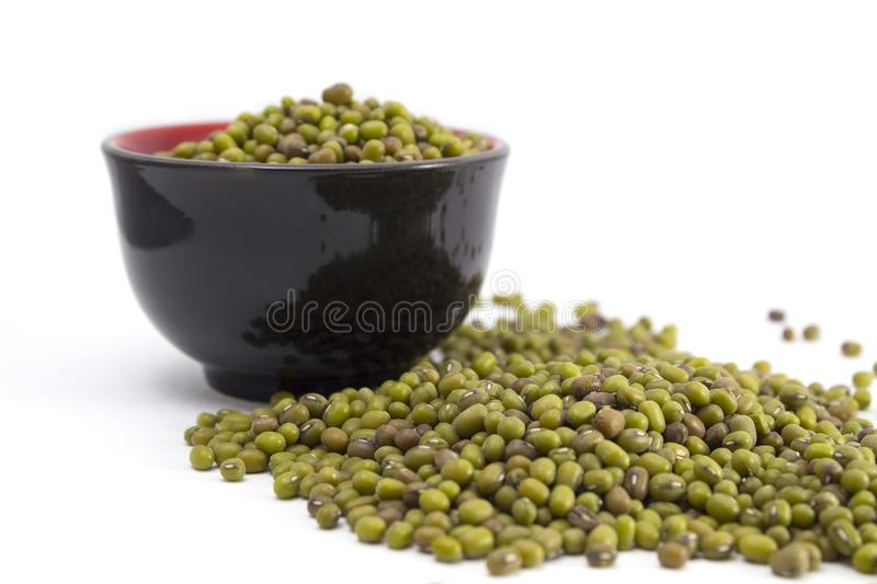 Green mung beans in a bowl. Black bowl of green mung beans. Background. Isolated stock image