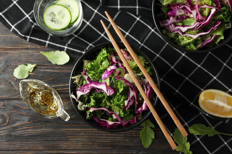 Black bowls with salad, chopsticks and towel on wooden background royalty free stock photography