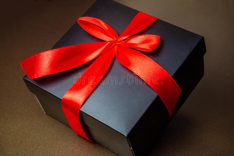 Black box with a red ribbon and bow on a gold background. Abstract: gift, intrigue, surprise stock photo