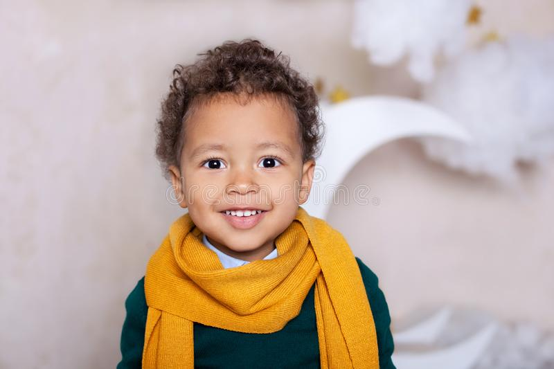 Black boy close up Portrait . Portrait of a cheerful smiling boy in a yellow scarf. The baby is smiling. Little African American. royalty free stock photo