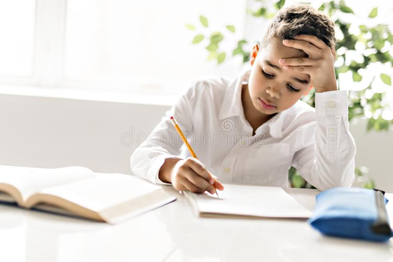A cute Black boy doing homework at home stock photo