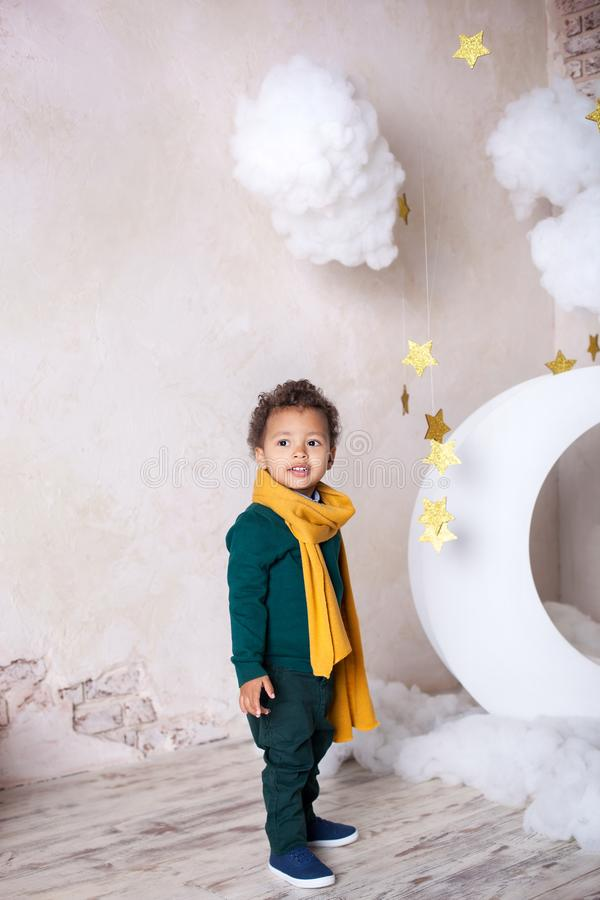 Black boy in a green sweater and a yellow scarf smiling. Portrait of a little African American. Baby smiles. A black boy stands ne royalty free stock images