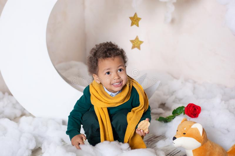 Black boy in a green sweater and a yellow scarf smiling. Portrait of a little African American. Baby smiles. Black guy The child e royalty free stock photo