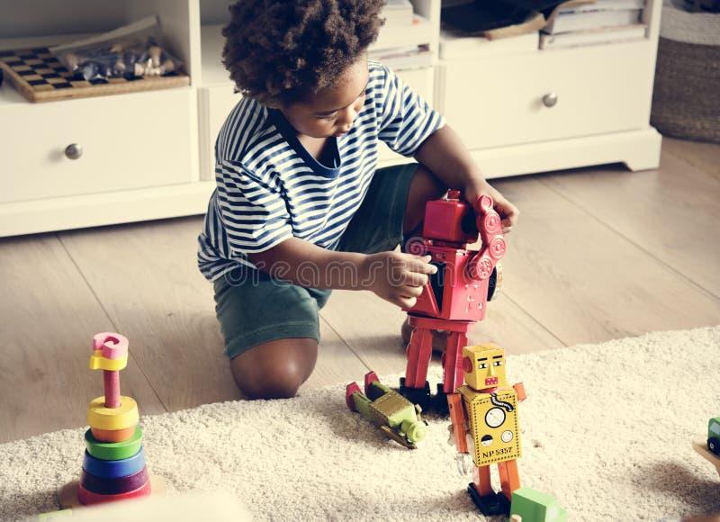 Black boy playing robots at home stock image