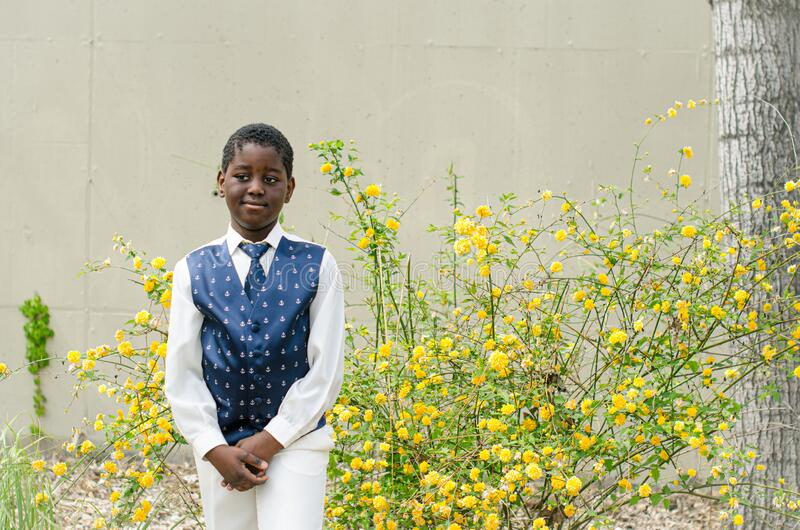Black boy, white shirt, tie and blue vest stock images