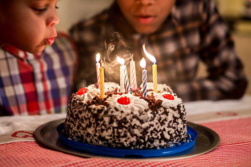 Black boys blow candles out. stock photos