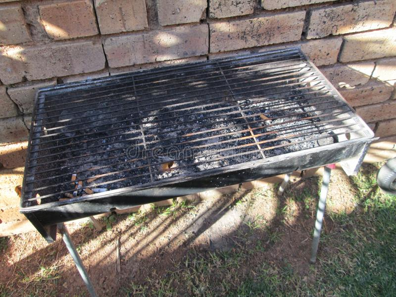 Black Braai Grill Barbecue in the Garden. Black braai, grill, barbecue with steel legs in front of a brick wall with cigarette butts, standing on the grass royalty free stock photo