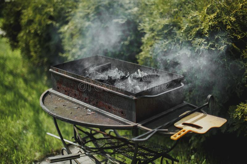 Black brazier with smoking coals in summer garden stock image