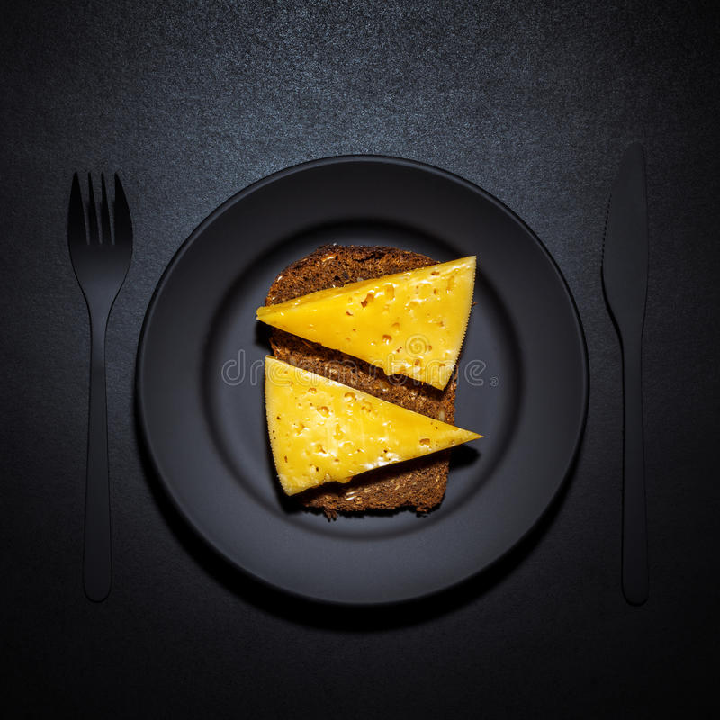 Black bread with cheese. On a black plate. View from above stock photography