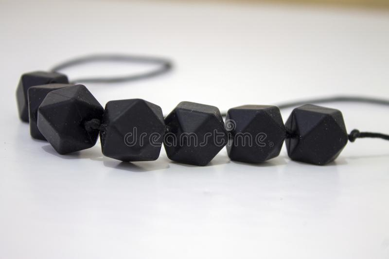 Black breast feeding necklace for baby and mom. Childhood growing up royalty free stock photo